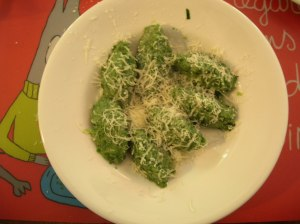 A dish with vegetable gnocchi served with grated parmesan