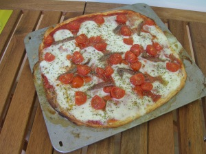 A home made pizza with anchovies and cherry tomatoes