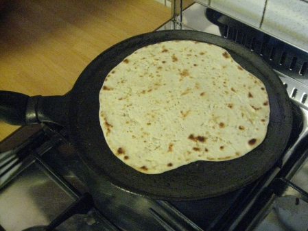 a piadina cooking on a hot-pan
