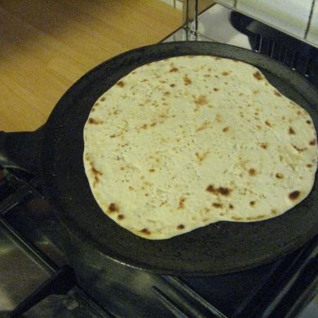 a piadina cooking on a hot-pan