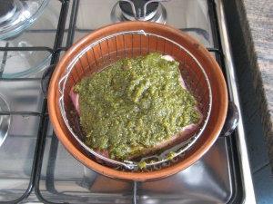 Raw pork tenderloin in a pot, covered with herb and garlic mince