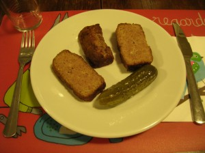 slices of meat loaf in a dish with a dill pickle